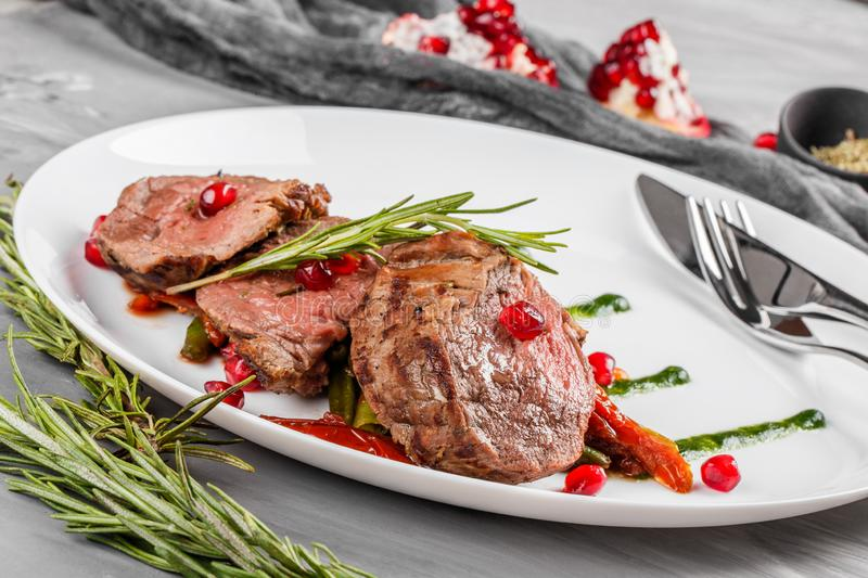 Juicy medium beef fillet steaks mignon with green beans, pomegranate and sauce in plate on grey background. Hot Meat Dishes, top view royalty free stock image