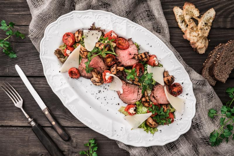 Juicy medium beef fillet steaks mignon with grilled vegetables, mushrooms, tomatoes, cheese in plate on rustic wooden background. Holiday Meat Dishes. Top view stock photo