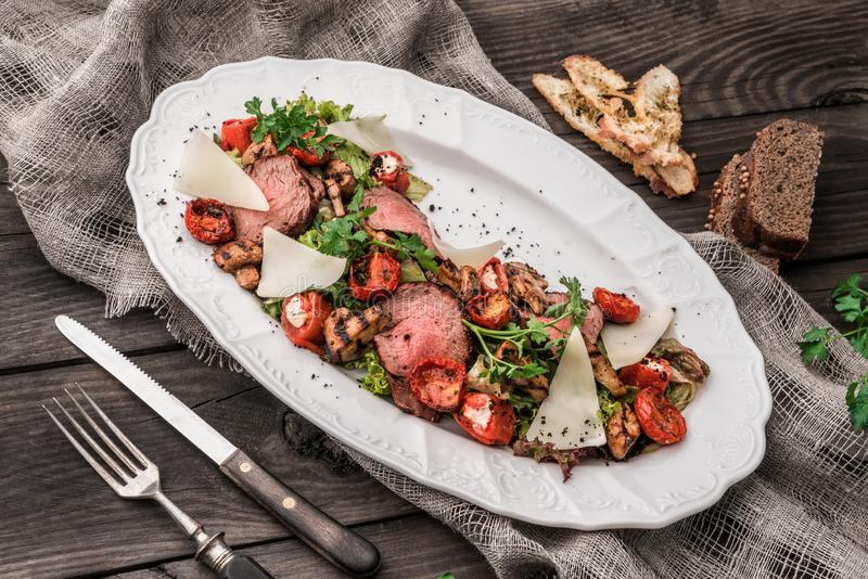 Juicy medium beef fillet steaks mignon with grilled vegetables, mushrooms, tomatoes, cheese in plate on rustic wooden background. Holiday Meat Dishes. Top view stock images