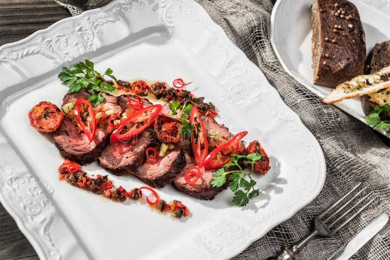 Juicy medium beef fillet steaks mignon with pepper, spices in plate on rustic wooden background. Hot Meat Dishes. Top view stock photos