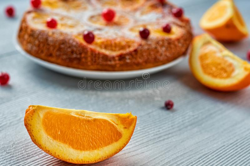 Juicy orange slice on the foreground close up with free copy space. Homemade orange cake with fresh red cranberries and oranges stock photos