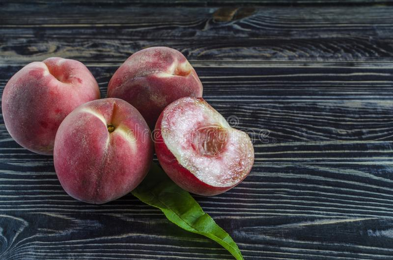 Juicy peaches on a dark wooden background and peach in a cut royalty free stock image