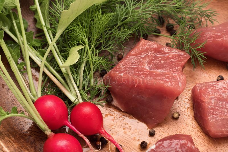 Juicy piece of meat served on a wooden plate with seasoning, herbs and vegetables royalty free stock photography