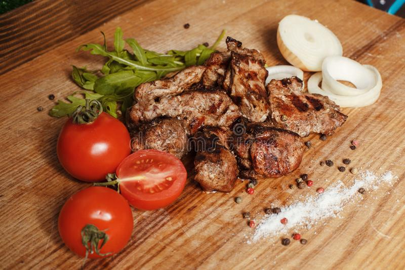 Juicy Pork Grilled. Juicy pork meat grilled. Close to the kebab lies fresh vegetables and onions royalty free stock images
