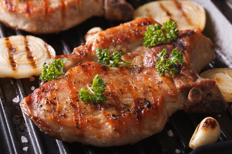 Juicy pork steak grilled with onions in a pan grill closeup. Juicy pork steak grilled with onions and garlic in a pan grill closeup. horizontal royalty free stock image