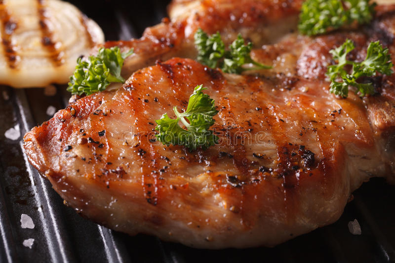 Juicy pork steak grilled with onions in a pan grill macro. Juicy pork steak grilled with onions and garlic in a pan grill macro. horizontal stock photography