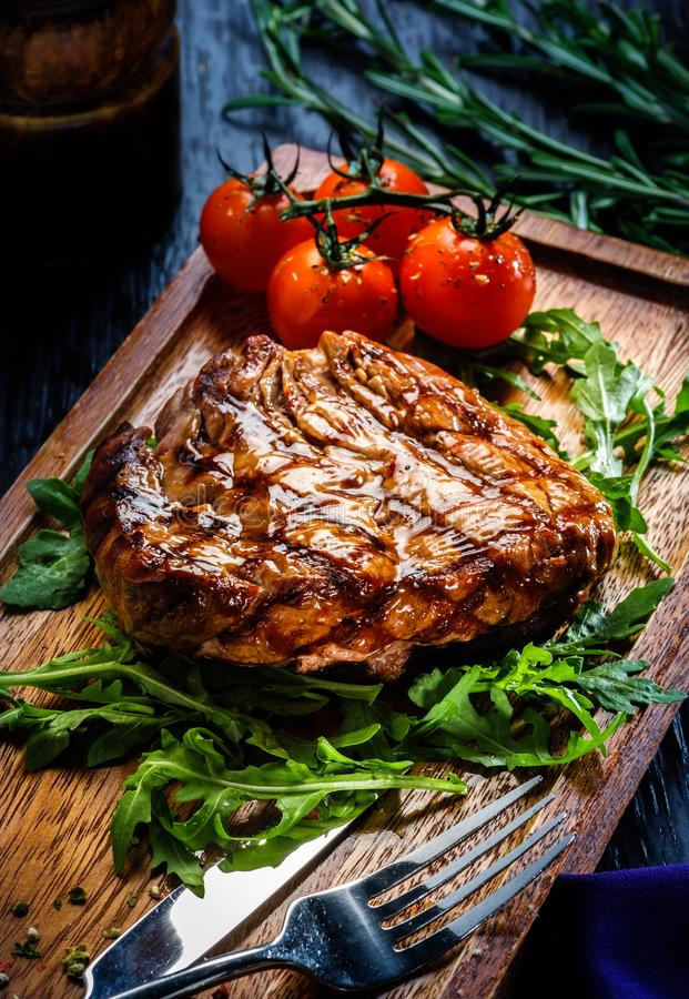 Juicy portions of grilled fillet steak served with tomatoes and stock photography