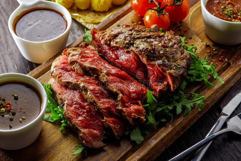 Juicy rare sliced grilled fillet steak served with tomatoes and stock photos