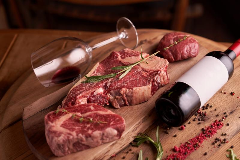 Juicy raw steaks of rib eye seasoned beef meat on a cutting board with a bottle of red wine, lying next to. A sprig of rosemary, peas, dried tomato. Shallow royalty free stock photos