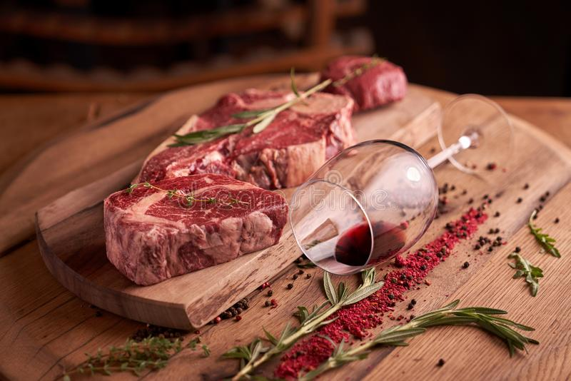 Juicy raw steaks of seasoned rib eye beef on a cutting board with a glass of red wine, lying next to. A sprig of rosemary, peppercorns, dried tomato royalty free stock images