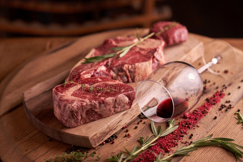 Juicy raw steaks of seasoned rib eye beef on a cutting board with a glass of red wine, lying next to. A sprig of rosemary, peppercorns, dried tomato stock images
