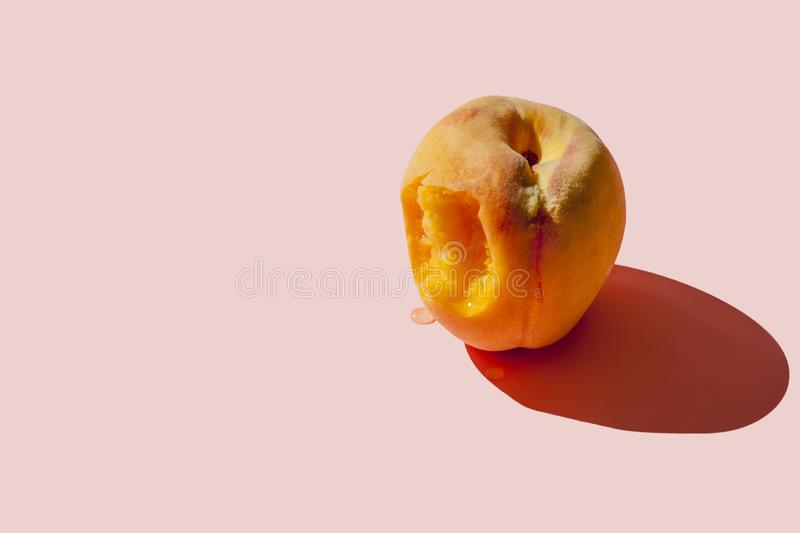 Juicy ripe bitten peach on a pastel pink background with a hard shadow. Copy space. Juicy ripe bitten peach on a pastel pink background with a hard shadow stock photography