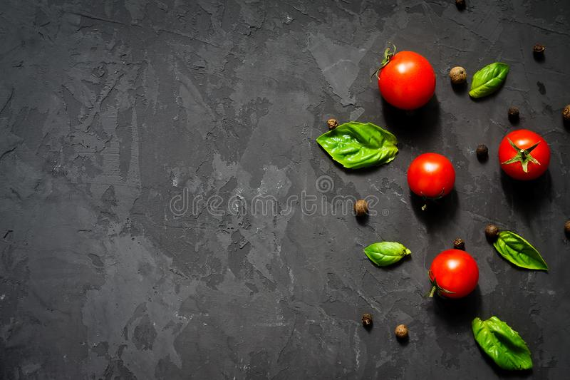 Juicy ripe cherry tomatoes with green basil leaves and black pepper on black background. Health food concept. Top view, copy space royalty free stock photography