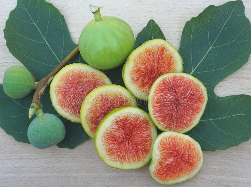 Juicy ripe figs, sliced on a background of fig leaves and one whole on the top stock photography