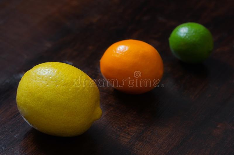 Juicy ripe lemon, citrus meyeri and lime on wooden background. Citrus fruit on a dark table. Beautiful fresh fruit. Food. Background. Top view close up royalty free stock photos