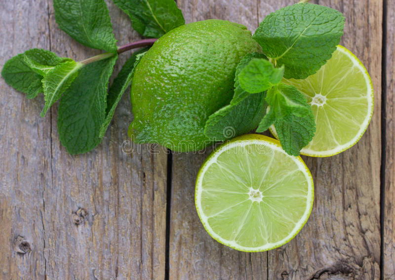 Juicy ripe limes. And mint on wooden table royalty free stock image