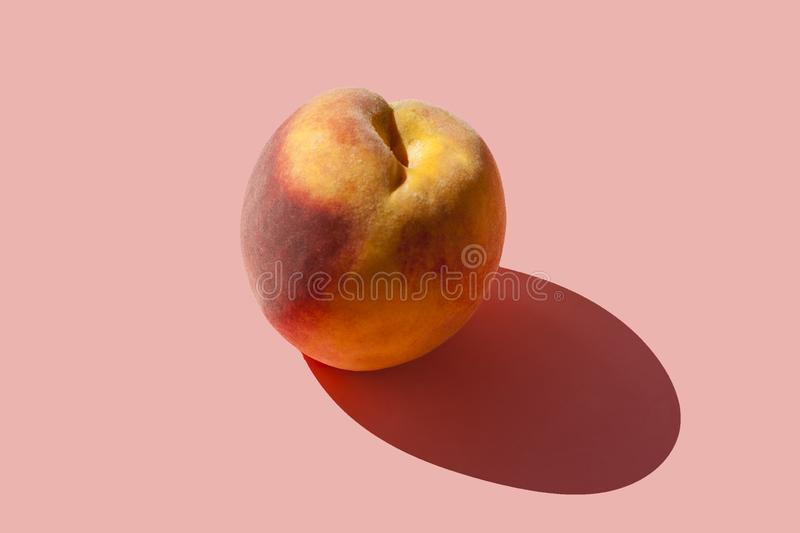 Juicy ripe peach on a pastel pink background with a hard shadow.  royalty free stock photos