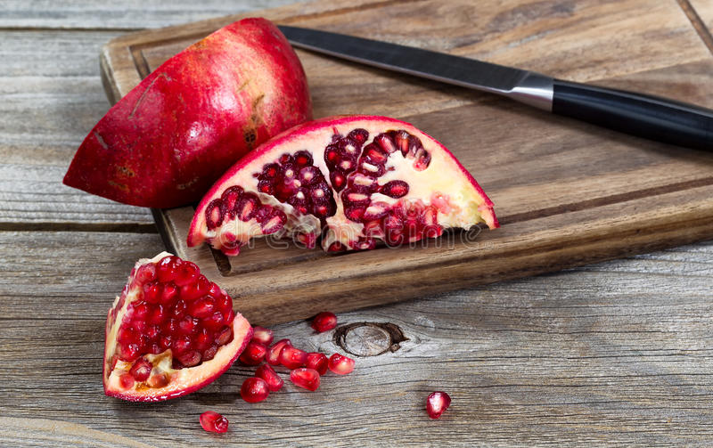Juicy ripe pomegranates with knife on vintage wood server royalty free stock images