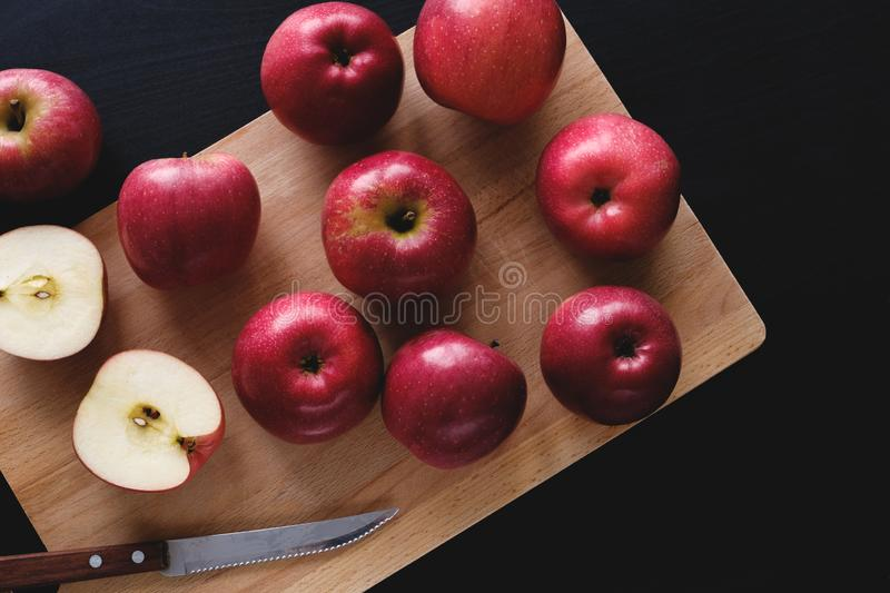 Juicy ripe red apples on wooden Board on black background. Cut the Apple in half. Next to the knife with a wooden handle. Proper stock photo