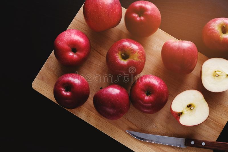 Juicy ripe red apples on wooden Board on black background. Cut the Apple in half. Next to the knife with a wooden handle. Proper royalty free stock photo