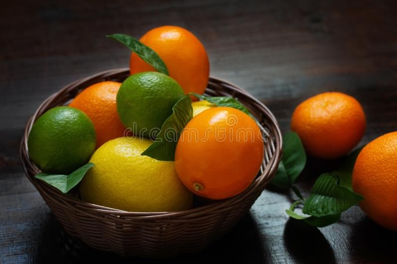 Juicy ripe slices of orange, lemon, grapefruit and lime on a dark background. Sliced citrus in a basket on a brown wooden table. Fruit mix, top view close-up stock photography
