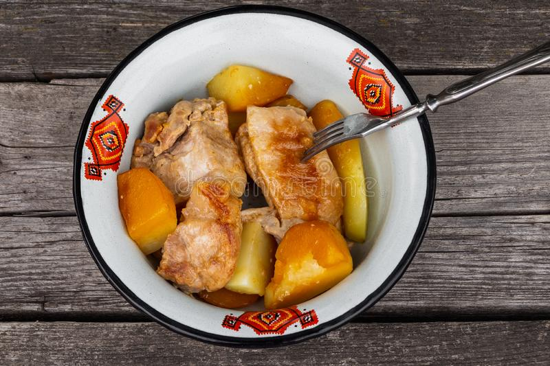 Juicy roast meat with potatoes served in a white metal bowl with a red ornament with a fork on an old rough gray wooden background. Juicy roast meat with golden royalty free stock photos