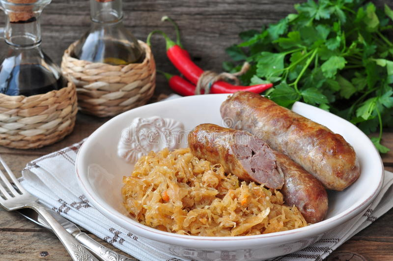 Juicy Roasted Bavarian sausages with the stewed cabbage royalty free stock image