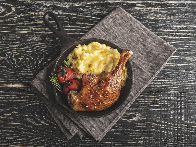 Juicy roasted duck leg with tomato, mashed potatoes in a serving fry pan.  royalty free stock photography