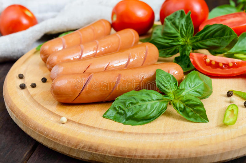 Juicy sausages with tomatoes and basil on a round cutting board on a dark wooden background royalty free stock photos