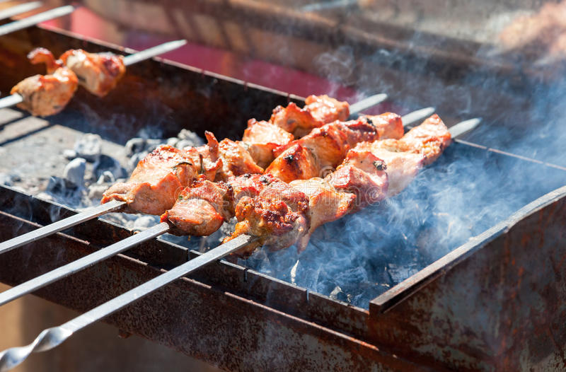 Juicy slices of meat with sauce prepare on the coals royalty free stock photos