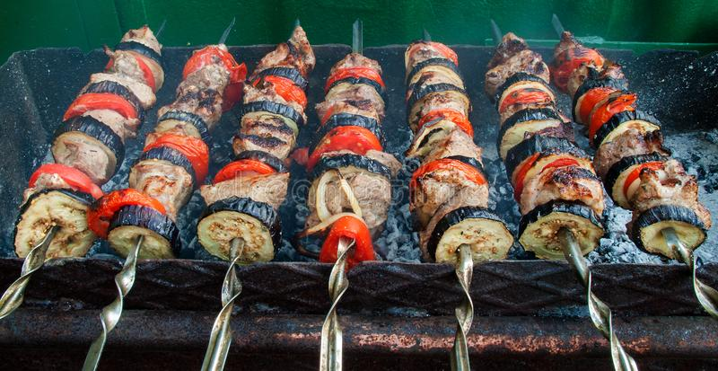 Juicy slices of meat with sauce prepare on fire shish kebab royalty free stock images
