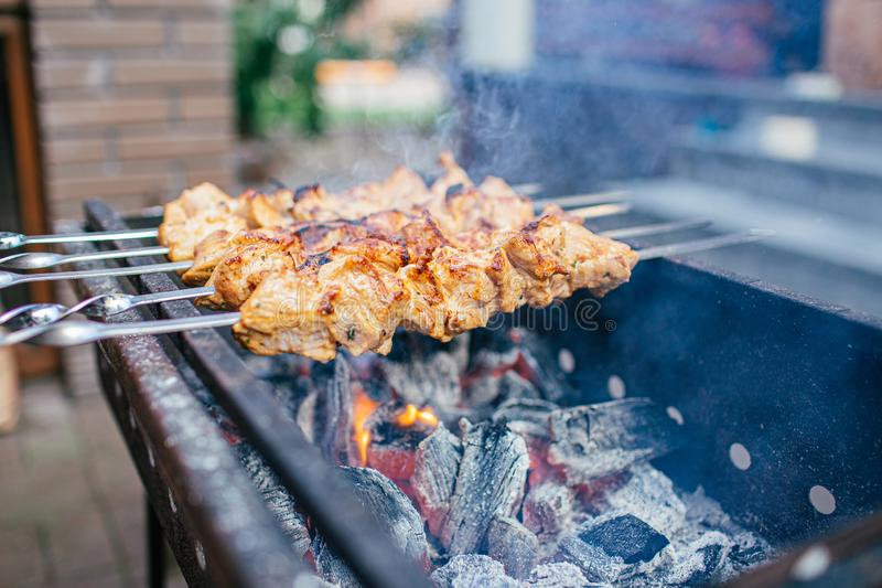 Juicy slices of meat with sauce prepare on fire shish kebab . BBQ outside. royalty free stock photo