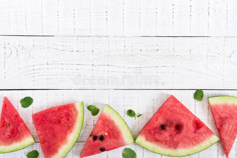 Juicy slices of a ripe watermelon on a white wooden background. Berry food background royalty free stock image