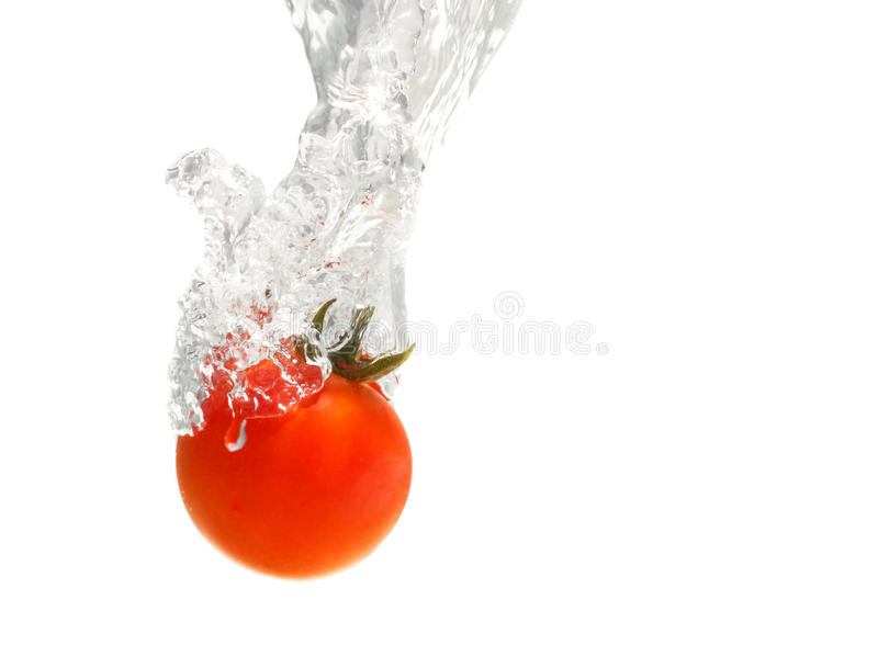 Juicy small cherry tomato dropped in water royalty free stock image