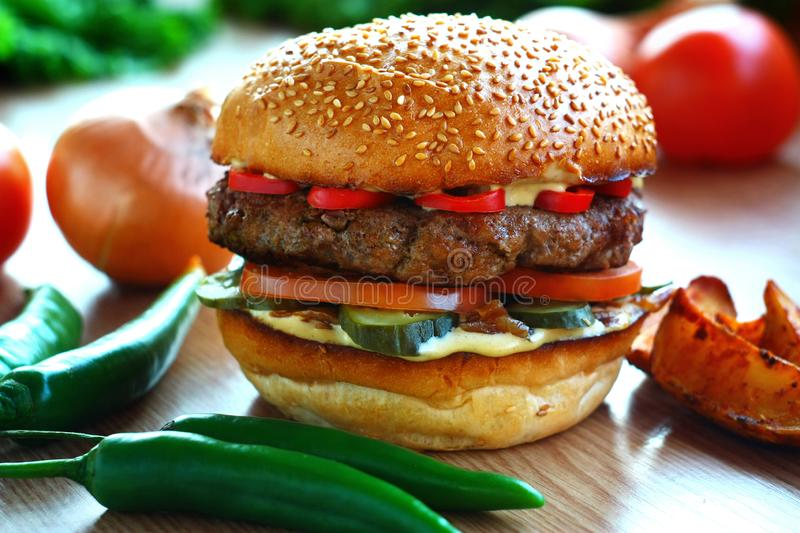 Juicy, spicy burger with beef and red pepper, on a table with vegetables. royalty free stock photos
