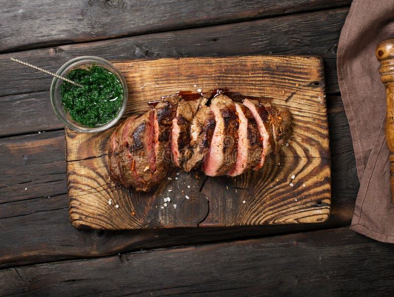 Juicy steak on cutting board with chimichurri sauce stock photo