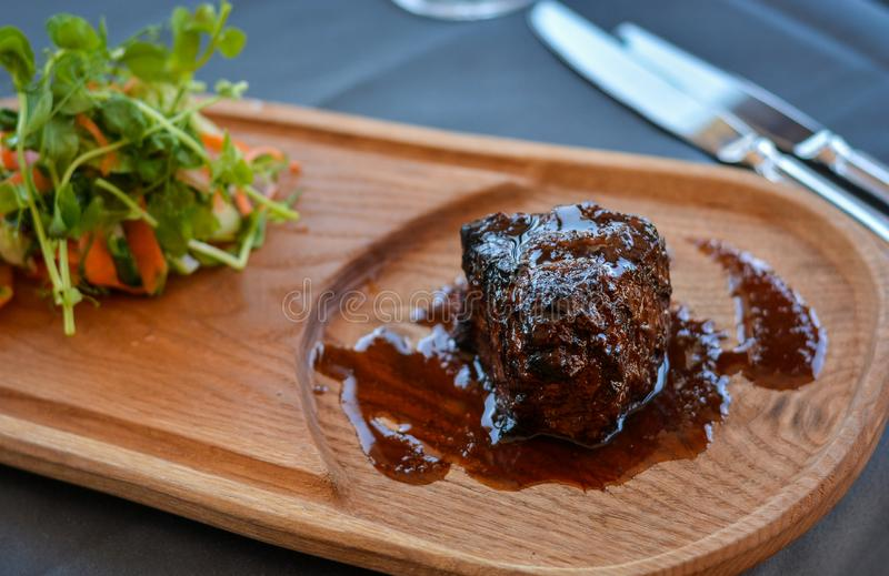 Juicy steak dish on wood plate with some greens on side in restaurant. Forks and knives on the side stock photo