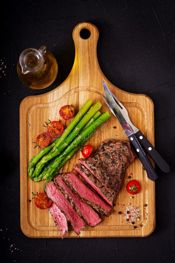 Juicy steak rare beef with spices on a wooden board and garnish of asparagus. stock photo