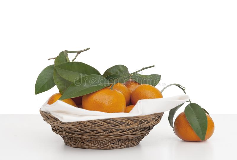 Juicy tangerines, small oranges with leaves in wicker basket with serviette, napkin. Fresh fruit on white, isolated. Against white background stock photo