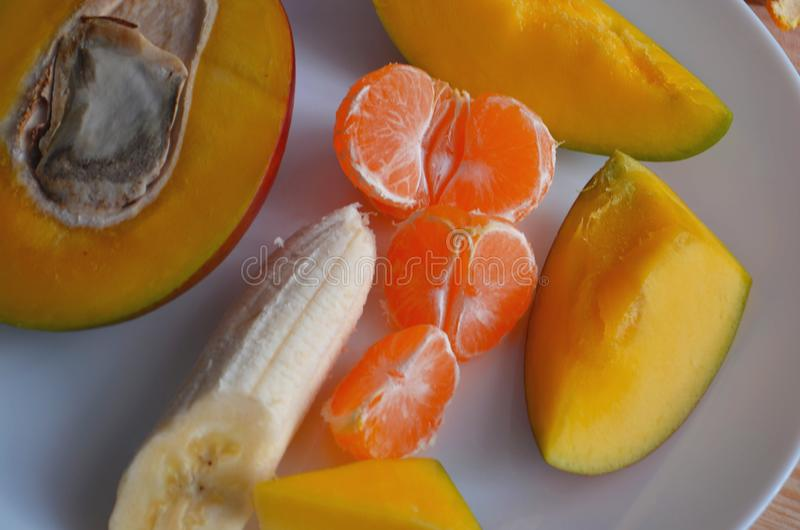 Juicy tangerines and tropical fruits on the New Year`s table. On a wooden background. Juicy tangerines and tropical fruits on the New Year`s table royalty free stock photos
