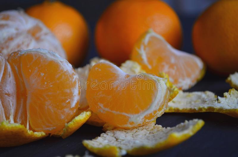 Juicy tangerines and tropical fruits on the New Year`s table. On a wooden background. Juicy tangerines and tropical fruits on the New Year`s table royalty free stock image