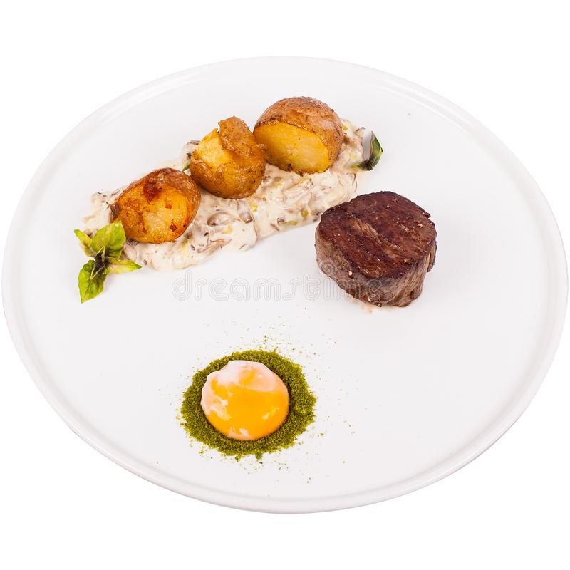 Juicy tenderloin medium cooked in herbs, served with fragrant potatoes and creamy mushroom sauce and egg isolated on white plate stock photo