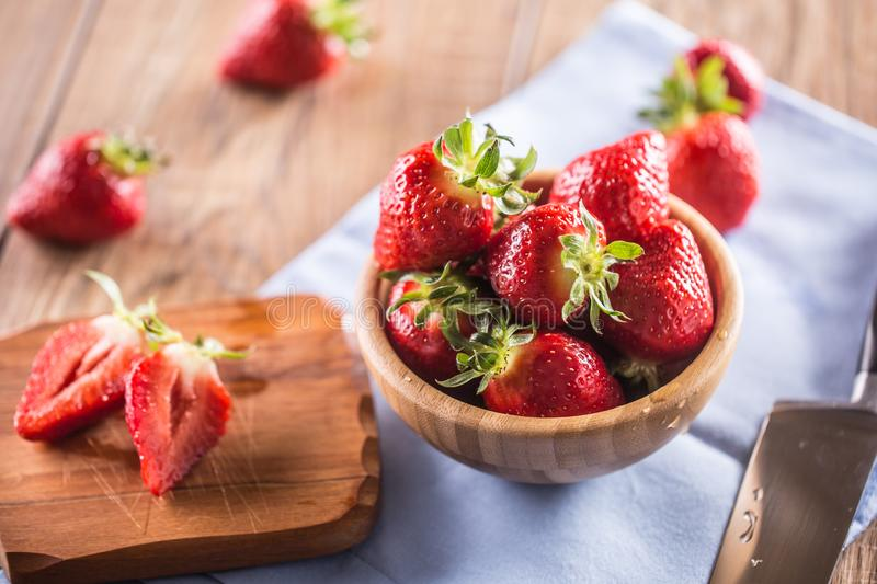 Juicy washed strawberries in wooden bowl on kitchen table royalty free stock photo