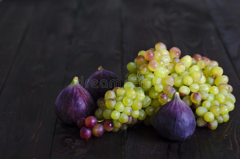 Juicy yellow, green raisins and several ripe blue figs on a dark wooden background. fresh fruits, natural vitamin, vegetarian food stock photos