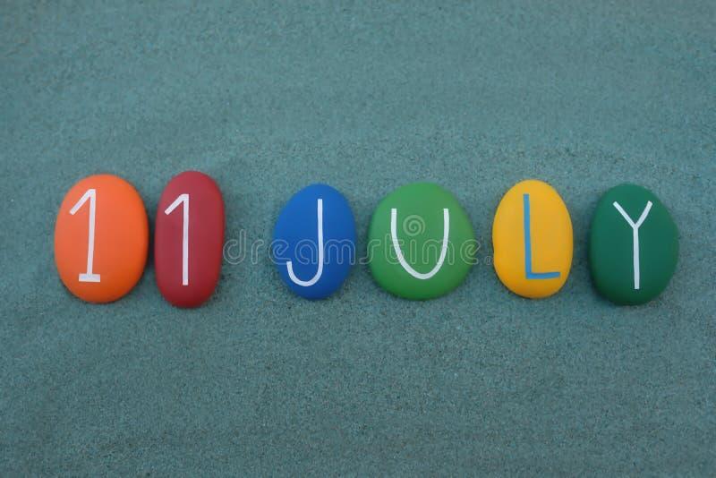 11 juillet, date civile composée avec les pierres colorées multi au-dessus du sable vert photographie stock libre de droits