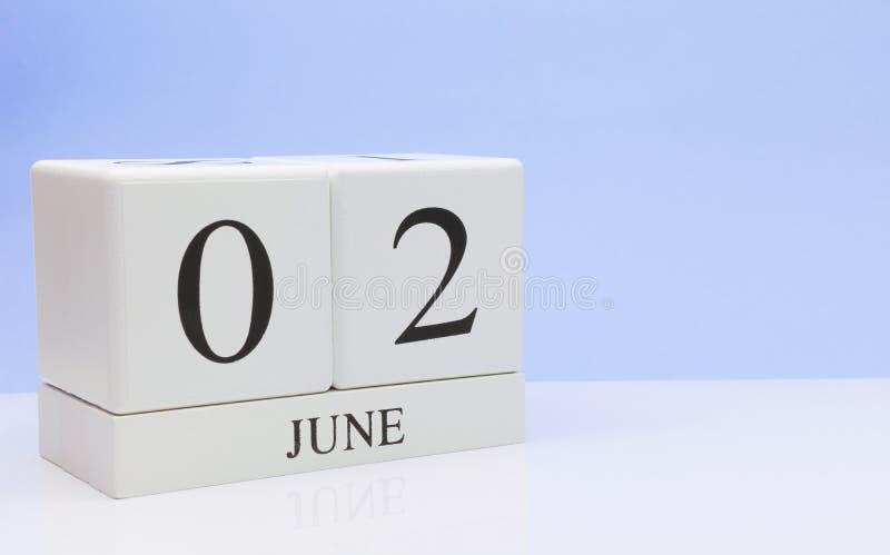 2 juin jour 2 du mois, calendrier quotidien sur la table blanche avec la réflexion, avec le fond bleu-clair Heure d'été, l'espace image libre de droits