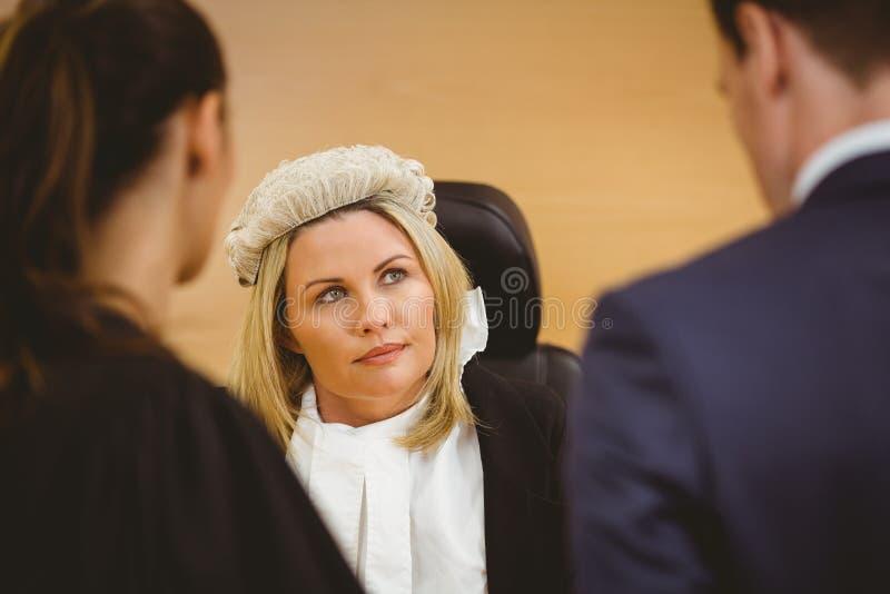 Juiz e advogado que escutam o criminoso nas algemas imagens de stock