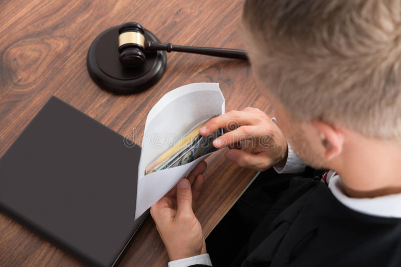 Juiz Looking At Money na sala do tribunal imagens de stock royalty free