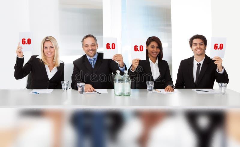Juizes do painel que guardam sinais perfeitos da contagem fotografia de stock