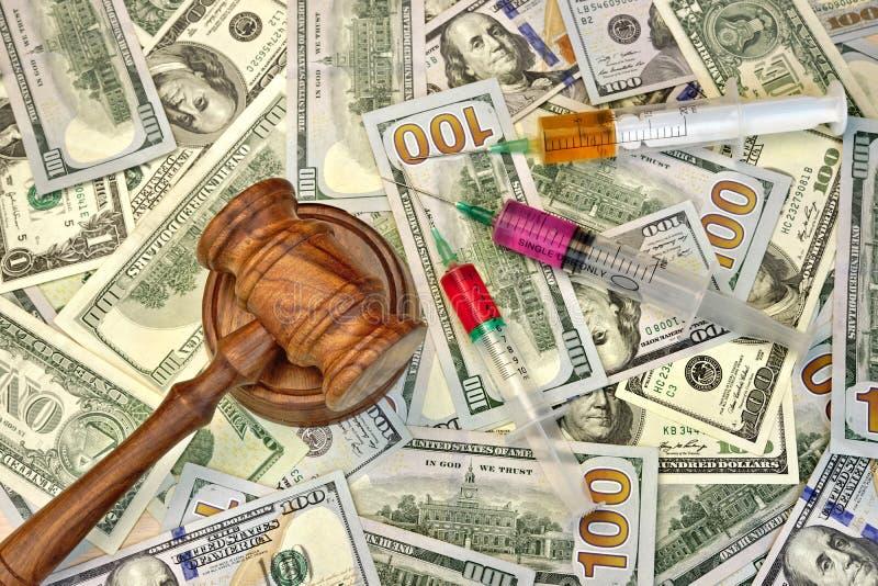 Juizes martelo e seringa com injeção no dinheiro Backgroun do dólar fotografia de stock